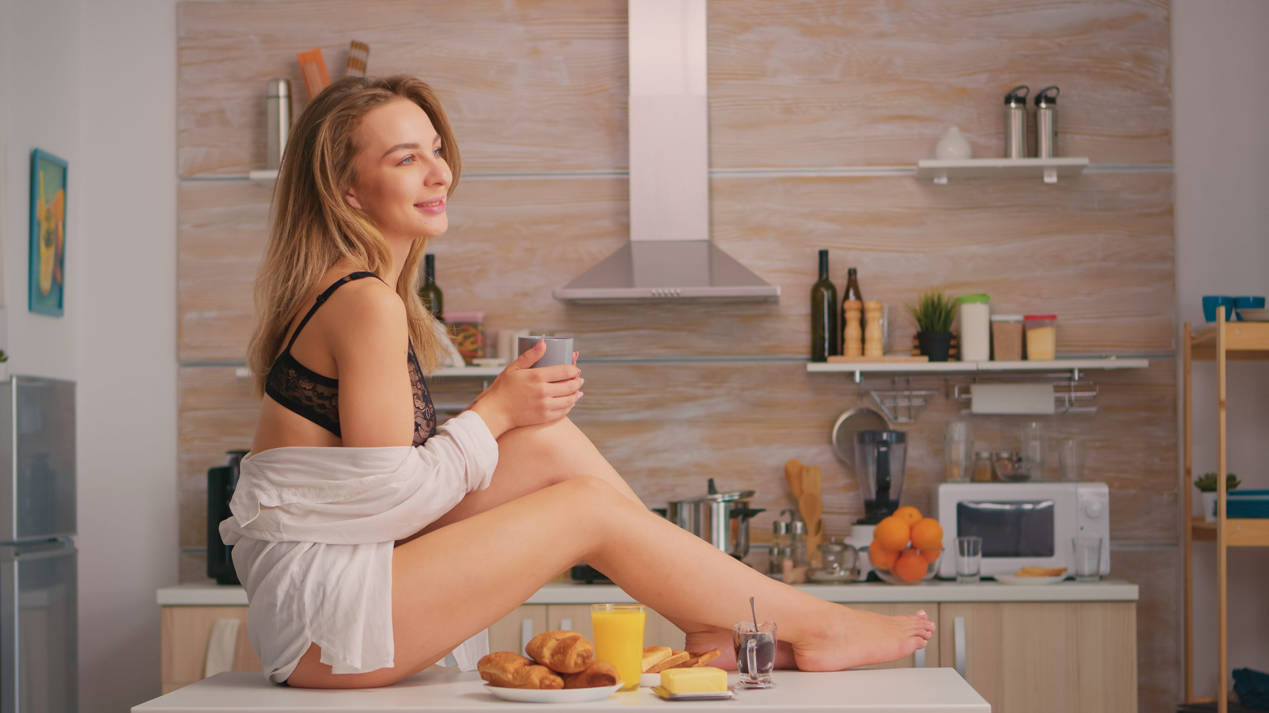 woman drinking coffee while sitting on her kitchen counter