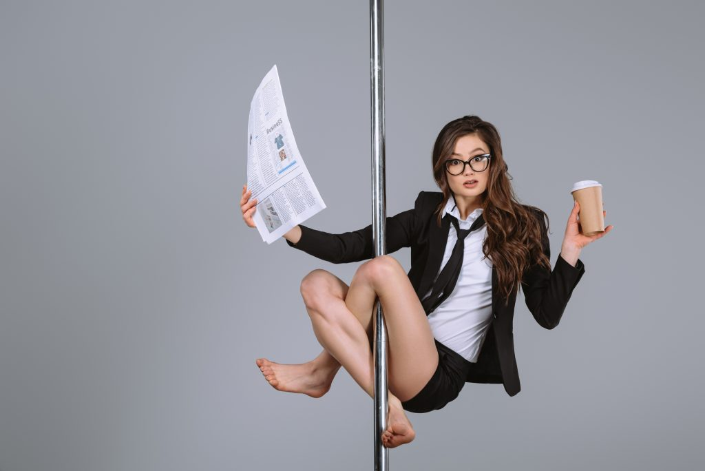 business woman dancing on a pole while balancing a business report and a coffee