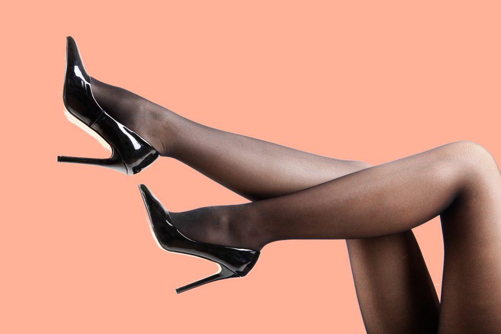 woman's legs wearing dark Pantyhose and black high heels